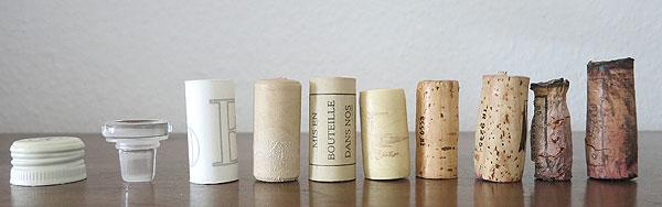 Das Foto zeigt (von links nach rechts): Schraubverschluss, Glasverschluss (Vinolok), Kunststoffstopfen, Granulat-Korken und Korken unterschiedlicher Länge und Alterung in der Flasche.